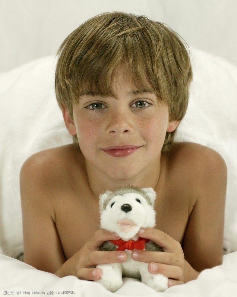 雀斑在床上拿着玩具的小男孩图片